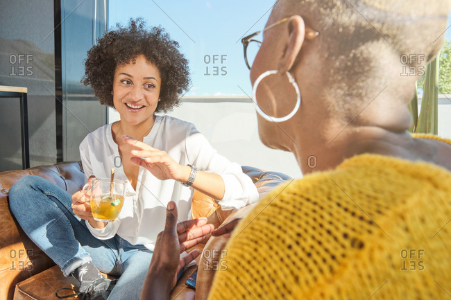 African American female with curly hair speaking to unrecognizable friend with short hair sitting on terrace and talking laughing at jokes and looking at each other while drinking hot beverage