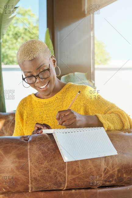 Pensive black female with short hair sitting in armchair on terrace and contemplating while writing thoughts in notebook