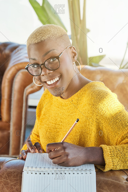 Cheerful black female with short hair sitting in armchair on terrace and contemplating while writing thoughts in notebook looking at camera