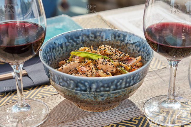 Bowl with appetizing chicken garnished with sesame and greenery served on table with red wine in Asian restaurant