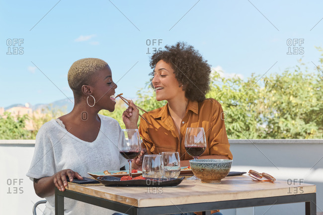 Cheerful African American female friends sitting at table on terrace of restaurant eating food with chopsticks while laughing and having fun together
