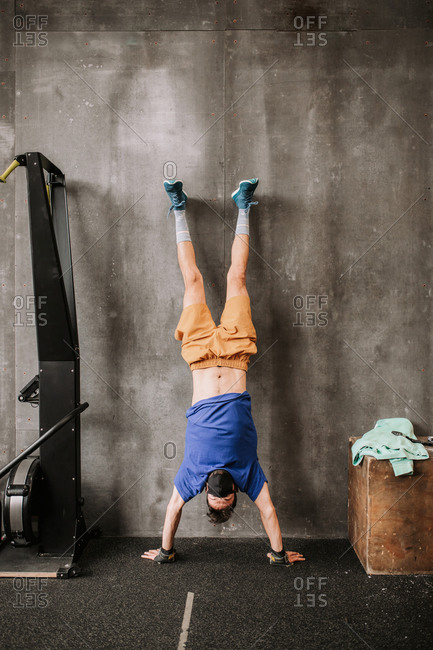Upside down view of athletic man in protective mask performing handstand near wall in modern gym during workout