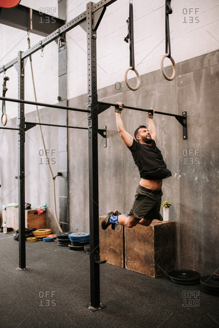 Determined male athlete making effort and pulling up on bar during active workout in gym