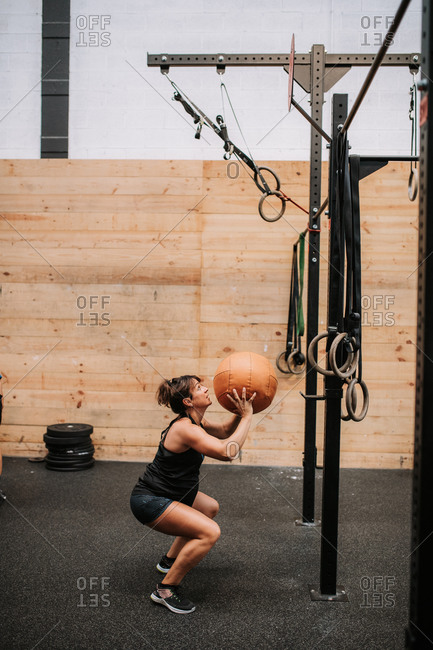 Side view of strong pregnant female athlete exercising with medicine ball in modern fitness center