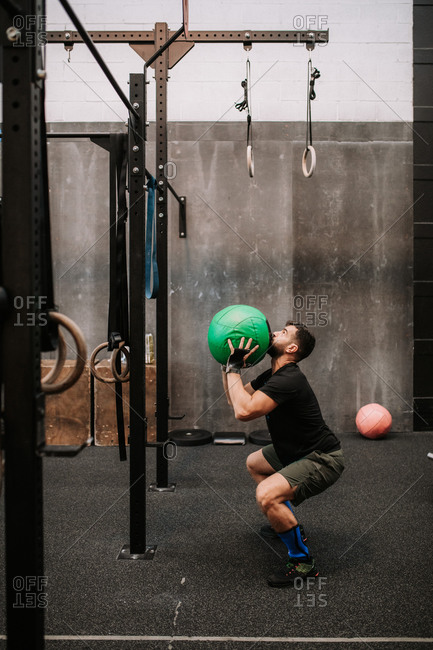 Side view of strong male athlete exercising with medicine ball in modern fitness center
