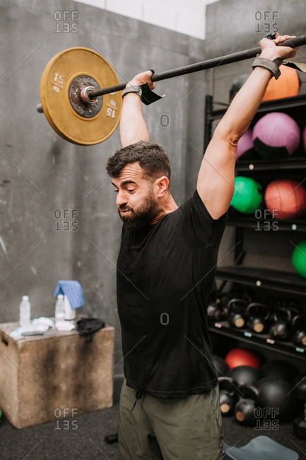 Side view of muscular male athlete doing clean and jerk exercise while training in modern fitness center