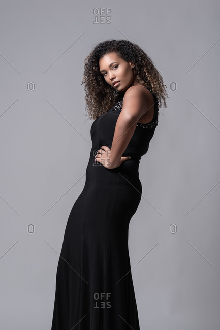Seductive young plus size African American female model with long curly hair wearing elegant black dress standing on studio looking at camera against gray background
