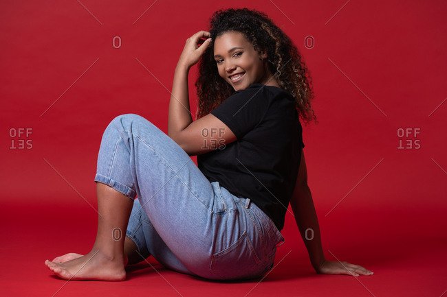 Full body of happy young overweight African American woman in casual black shirt and jeans with bare feet sitting in red studio looking at camera