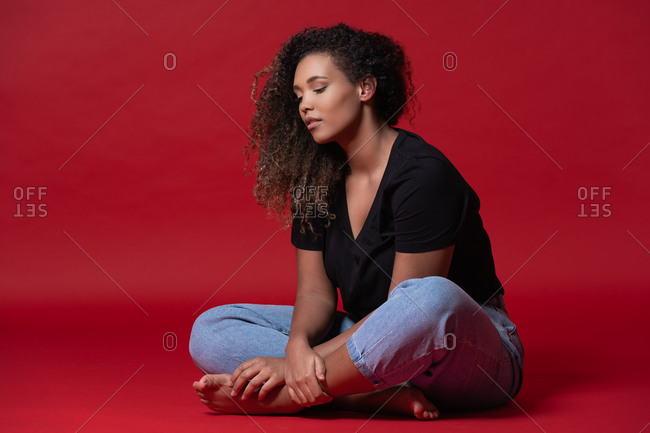 Full body of young overweight African American woman in casual black shirt and jeans with bare feet sitting in red studio looking down