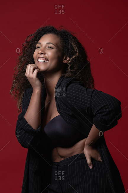 Beautiful confident happy young plus size black female model with long curly hair wearing elegant black dress looking away against red background