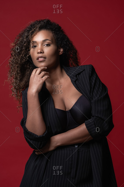 Beautiful confident young plus size black female model with long curly hair wearing elegant black dress looking at camera against red background