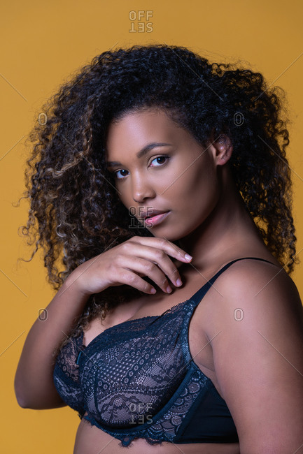 Attractive African American overweight female model with long curly hair wearing delicate lace bra looking at camera against yellow background