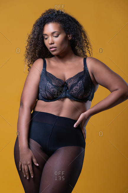 Attractive African American overweight female model with long curly hair wearing delicate lace bra looking down against yellow background