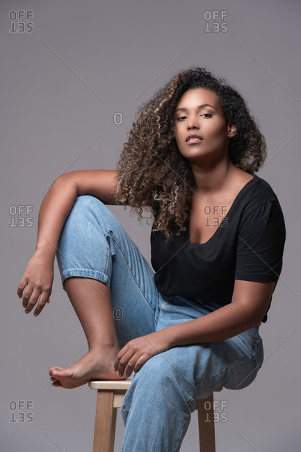 Plus size barefoot young African American female with curly hair dressed in jeans and black shirt sitting on chair and looking at camera against gray background