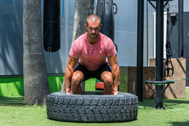 Muscular focused male athlete lifting heavy tire during active functional workout on sports ground