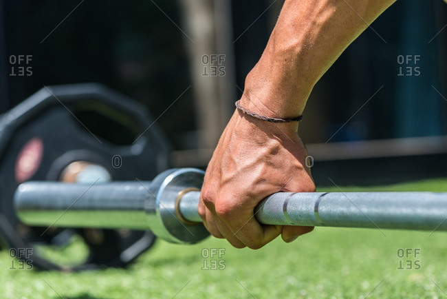 Determined athletic male in sportswear lifting heavy barbell during weightlifting training in summer