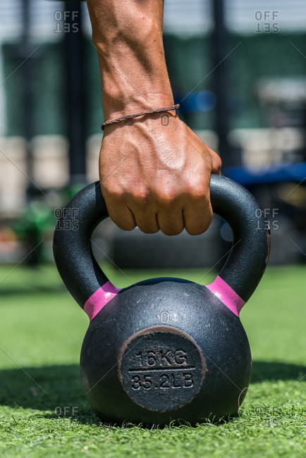 Athlete with strong body doing exercises with heavy metal kettlebell during intense workout in summer