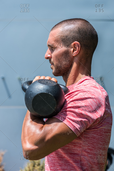 Side view male athlete with strong body doing exercises with heavy metal kettlebell during intense workout in summer