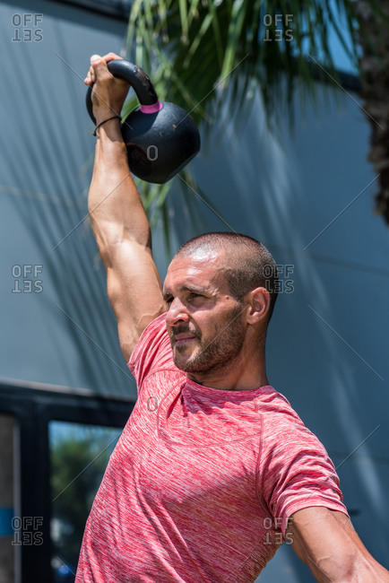 Serious male athlete with strong body doing exercises with heavy metal kettlebell during intense workout in summer
