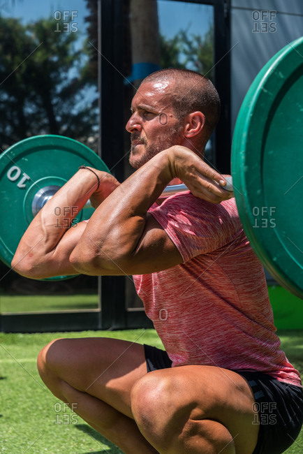 Side view of muscular male athlete lifting barbell and doing clean and jerk exercise during training on sunny day