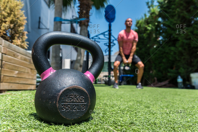 Ground level of heavy kettlebell placed on lawn on blurred background of strong male athlete doing swings with metal equipment during dynamic training