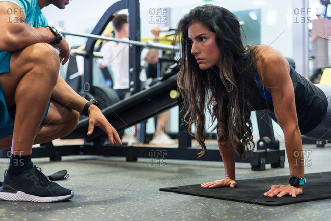 Focused ethnic female athlete doing push ups on mat under control of crop unrecognizable personal trainer in modern gym