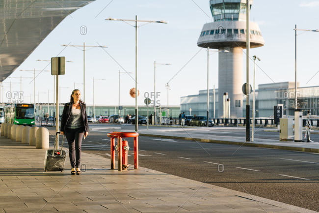 Cheerful female tourist with suitcase and backpack walking in airport and smiling away while enjoying summer weekend
