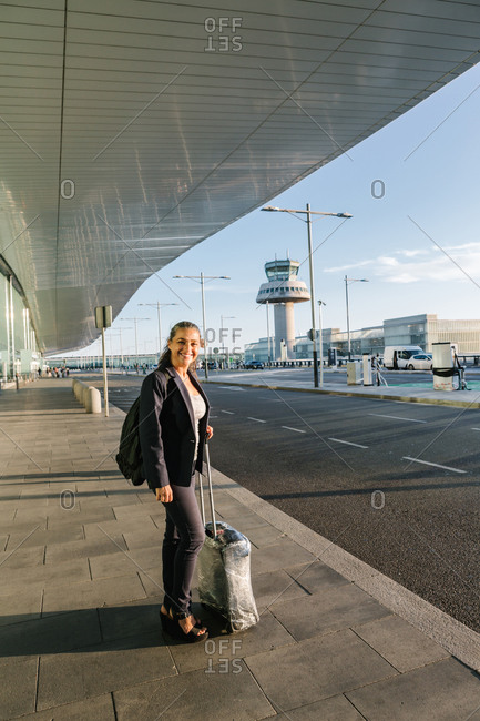 Cheerful female tourist with suitcase and backpack standing in airport and smiling at camera while enjoying summer weekend