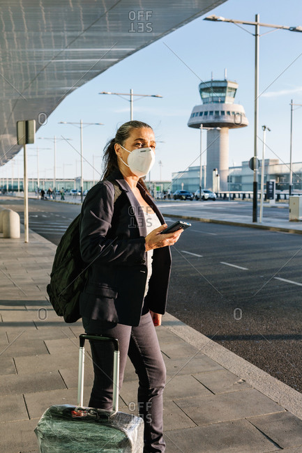 Traveling female wearing protective respirator during coronavirus epidemic standing with suitcase in airport after arrival and waiting for taxi while looking away