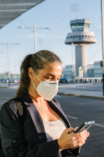 Traveling female wearing protective respirator during coronavirus epidemic browsing smartphone in airport after arrival and waiting for taxi