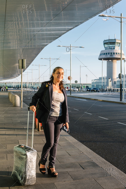 Cheerful female tourist with suitcase and backpack standing in airport and smiling away while enjoying summer weekend