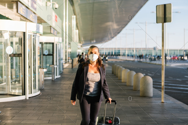 Cheerful female tourist in mask with suitcase and backpack standing in airport and smiling at camera while enjoying summer weekend