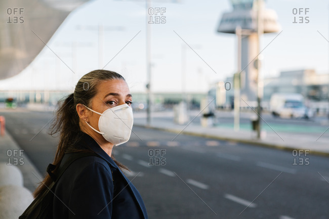 Female tourist in protective respirator during COVID 19 epidemic standing in airport and catching taxi with outstretched arm while looking away