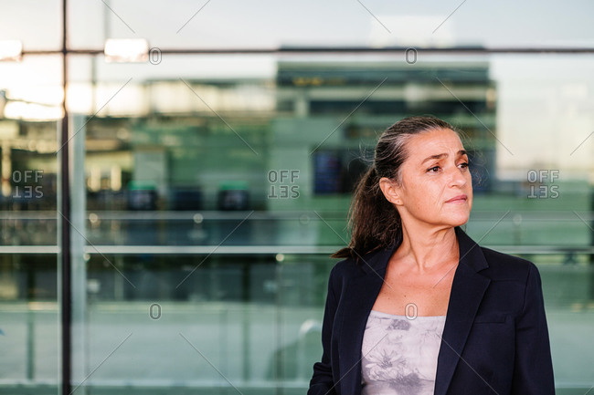 Cheerful female tourist with suitcase and backpack standing in airport and looking away while enjoying summer weekend