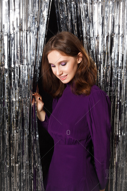 Young brunette woman dressed in a purple dress surrounded by silver tinsel looking down
