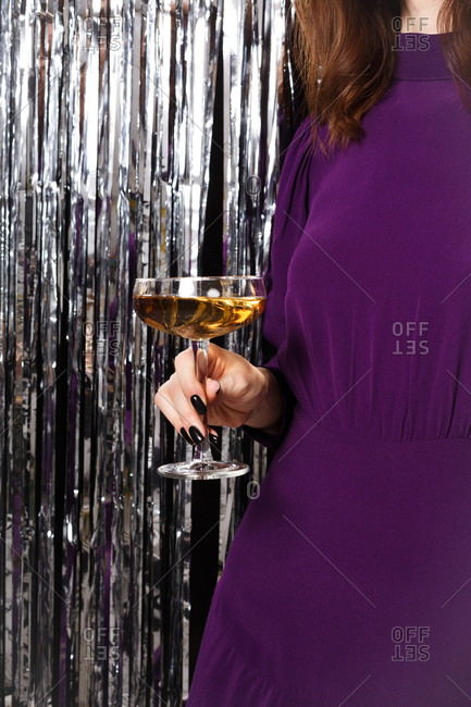 Close up of a young woman dressed in a purple dress surrounded by silver tinsel holding a coupe glass