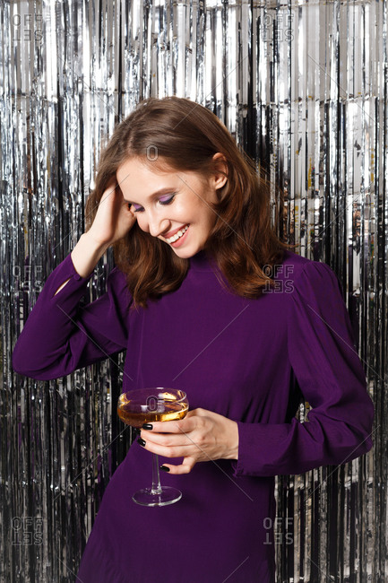 Young brunette woman dressed in a purple dress surrounded by silver tinsel holding a glass of wine