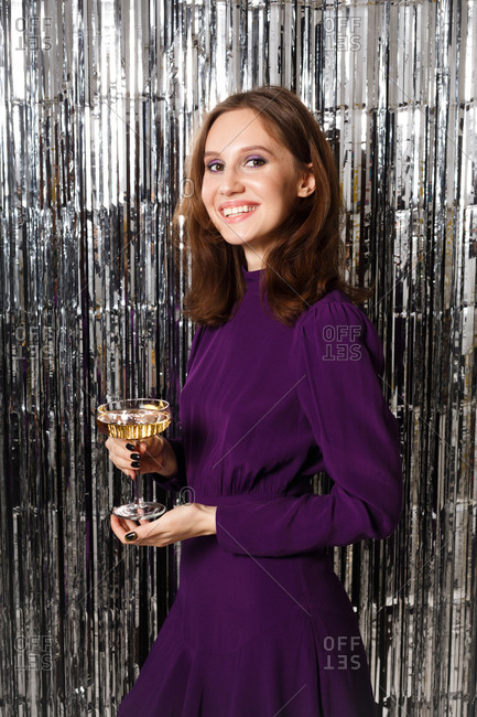 Woman dressed in a purple dress smiling while surrounded by silver tinsel holding a glass of wine