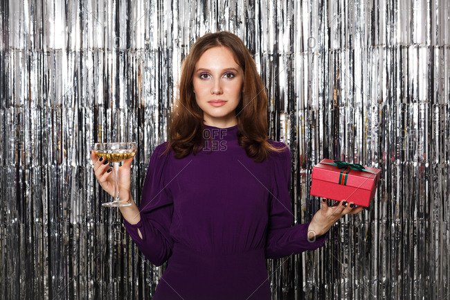 Woman wearing a purple dress holding a glass of wine and gift in front of a silver tinsel backdrop