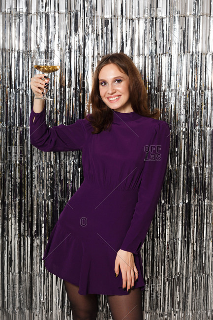 Young brunette woman in a purple dress surrounded by silver tinsel toasting with a glass of champagne