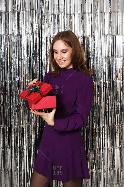 Happy young woman wearing a purple dress holding a gift in front of a silver tinsel backdrop