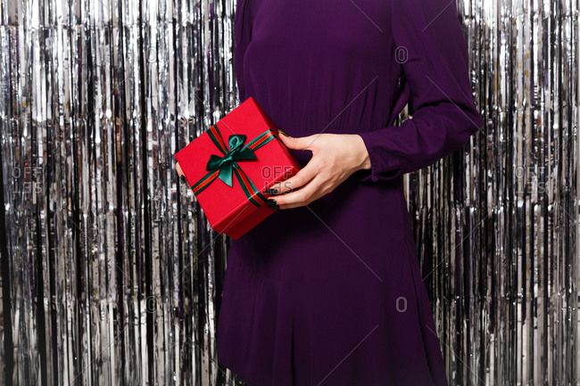 Close up of a young woman dressed in a purple dress surrounded by silver tinsel holding a red gift box