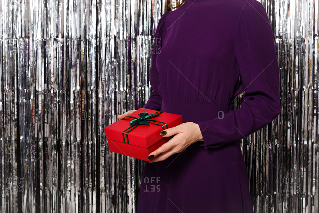 Woman in a purple dress holding a red gift box in front of tinsel backdrop close up