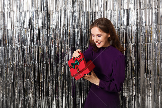 Smiling woman wearing a purple dress holding a gift in front of a silver tinsel backdrop