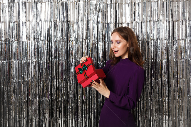 Woman wearing a purple dress making a surprised expression while opening gift in front of a tinsel backdrop