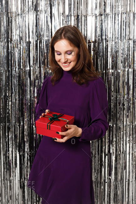 Young woman wearing a purple dress holding a red gift box in front of a silver tinsel backdrop