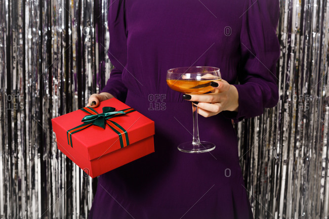 Close up of a woman in a purple dress surrounded by silver tinsel holding a red gift box and coupe glass