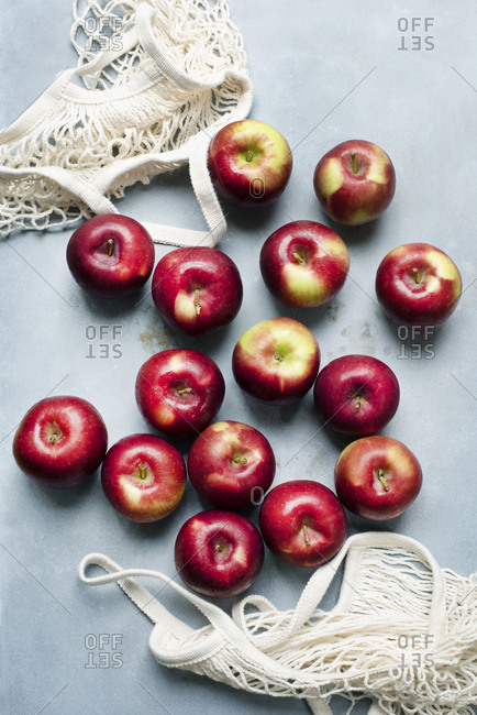 Red apples lying close to net bags