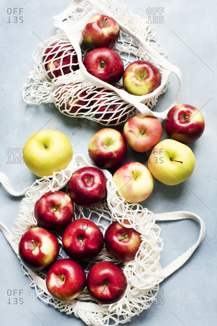 Red and yellow apples in off white net bags