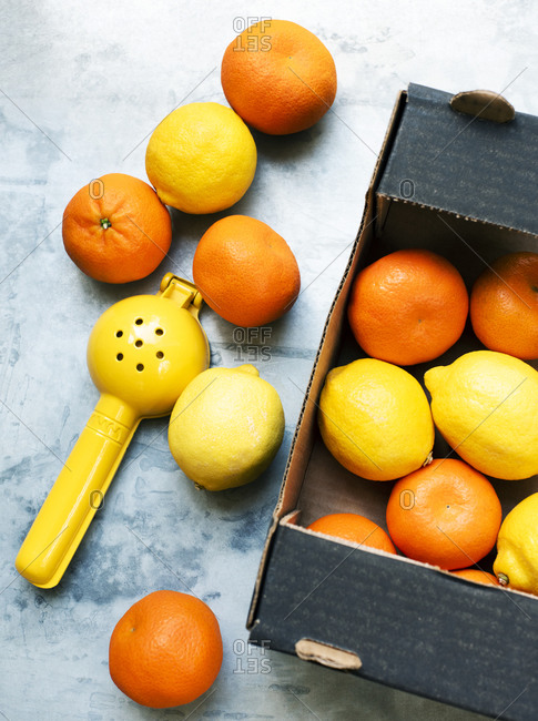 Oranges and lemons in paper box with squeezer